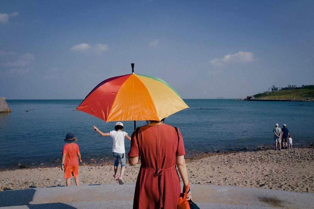 woman in orange dress holding umbrella walking on beach during daytime