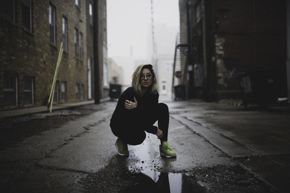 woman in black long sleeve shirt and black pants sitting on the sidewalk