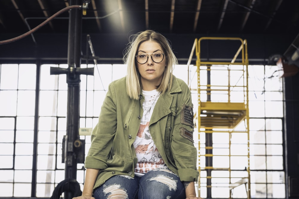 woman in green jacket and blue denim jeans sitting on black metal bar