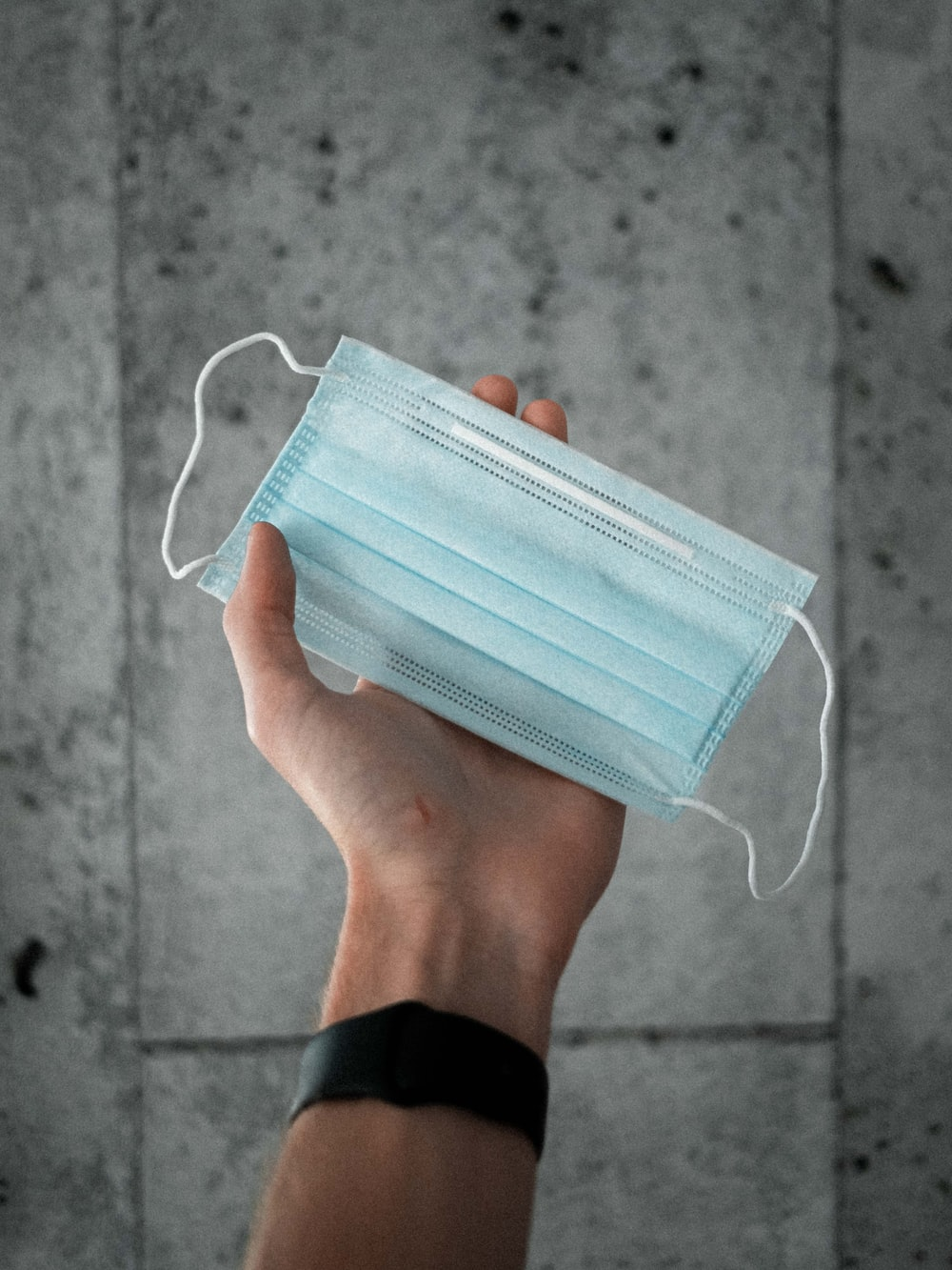 person holding blue and white striped pouch
