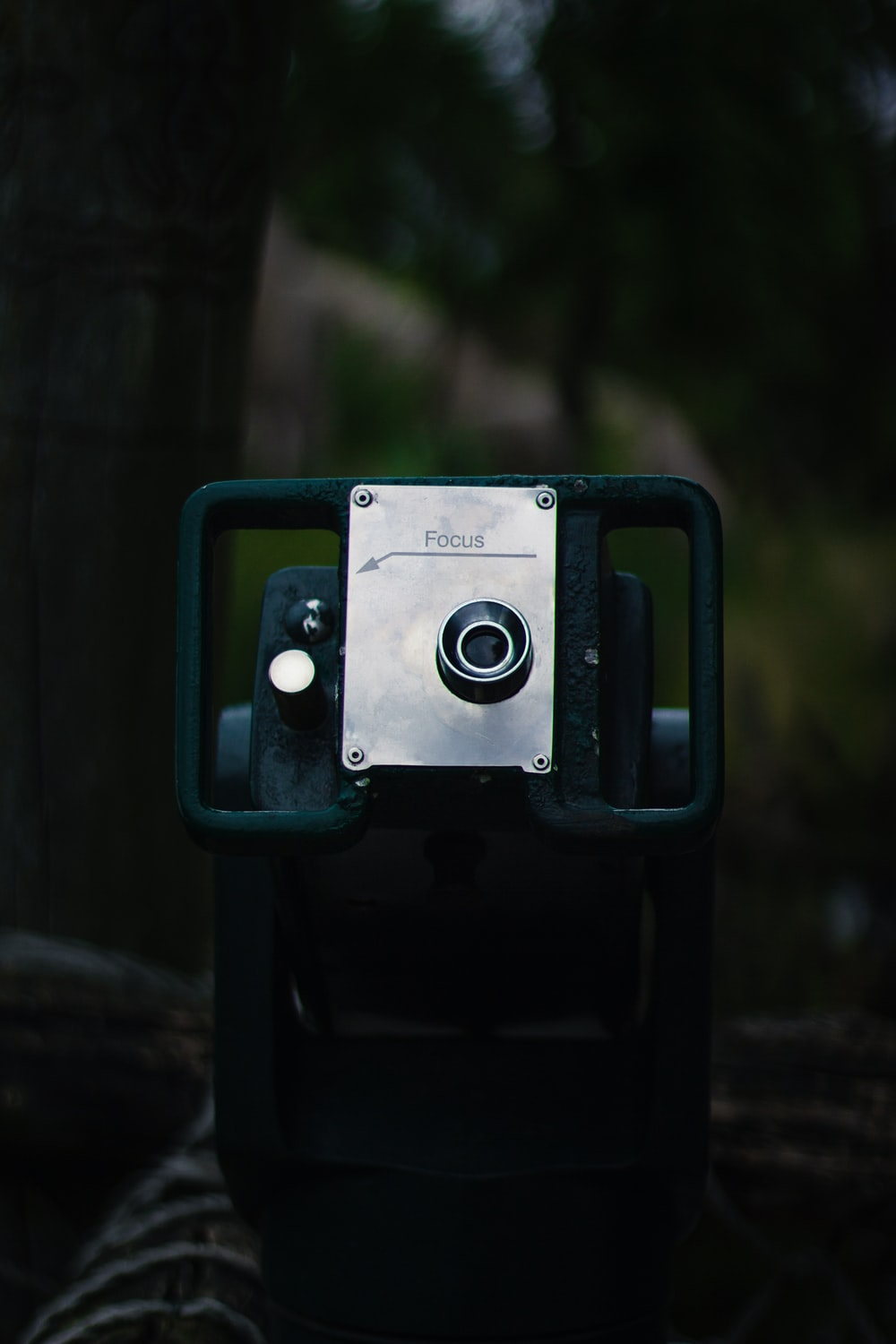 green and black camera on brown wooden surface