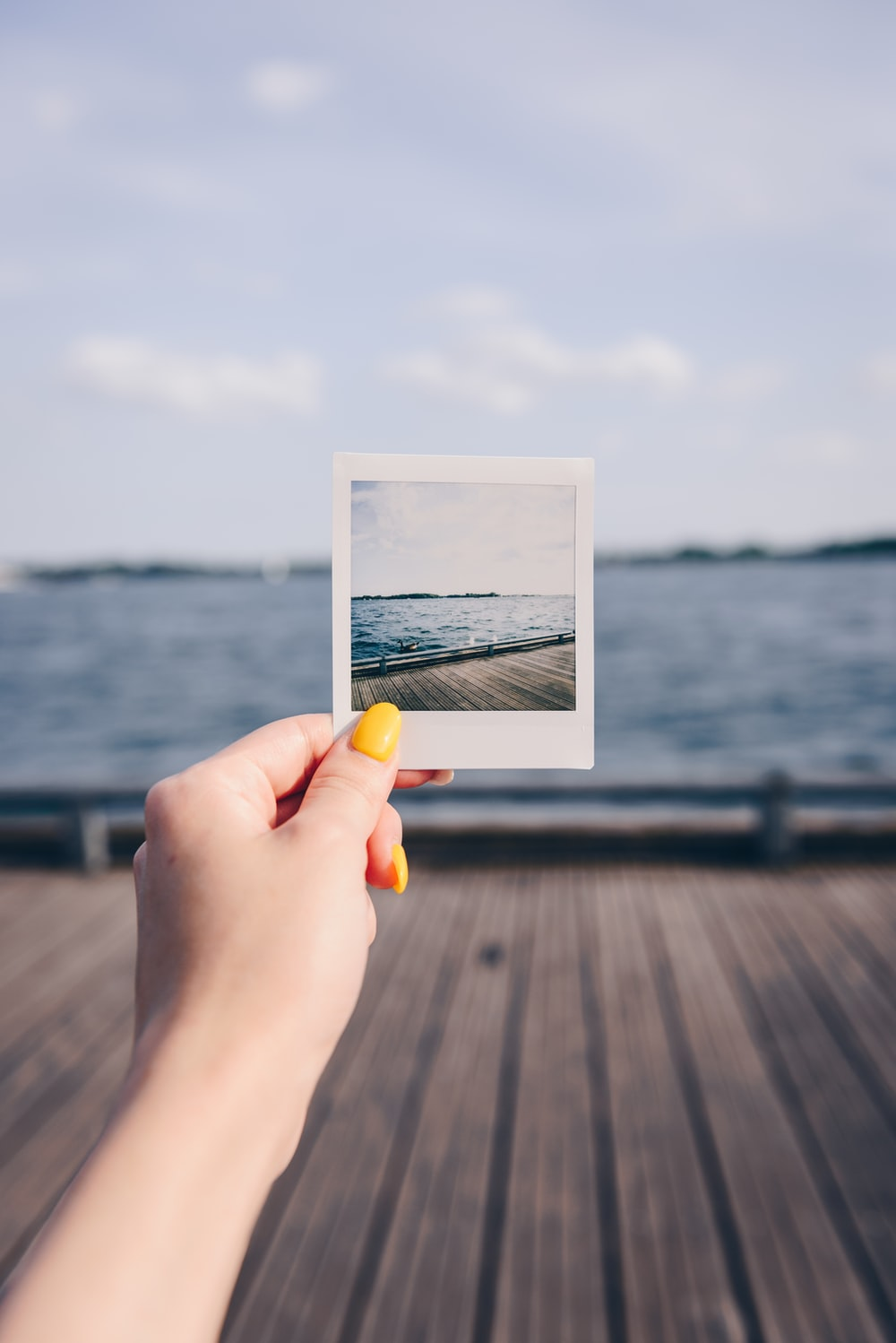 person holding white picture of body of water during daytime