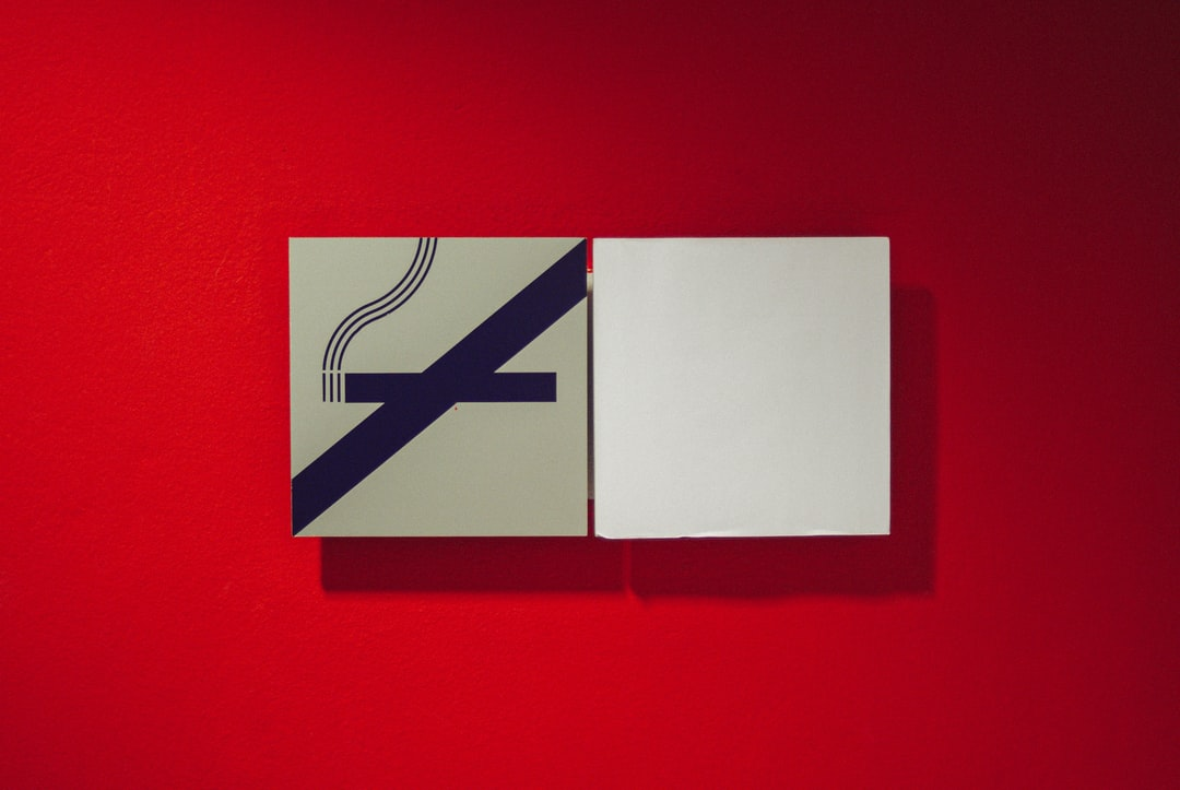 """The pictogram """"Do not smoke"""" and the white square against the red wall."""