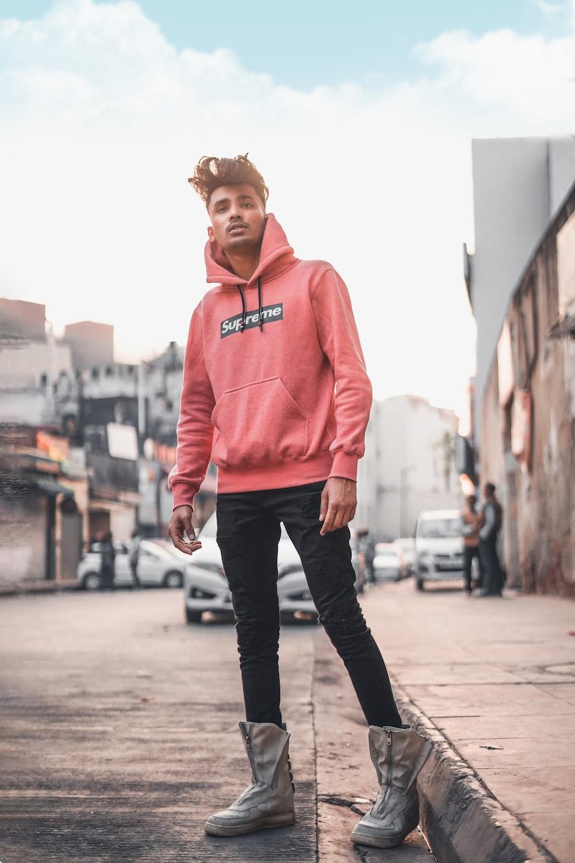 woman in pink pullover hoodie standing on sidewalk during daytime