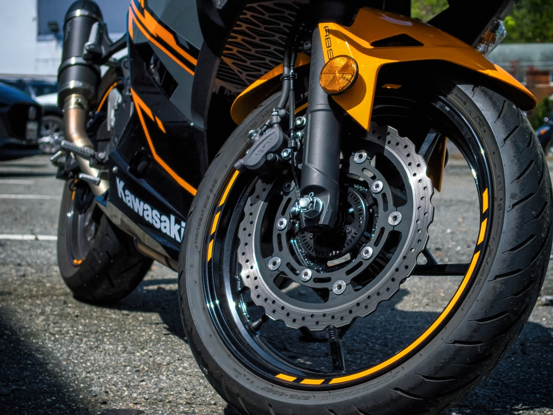 A Black and Grey Kawasaki Ninja with orange accents on a sunny day.