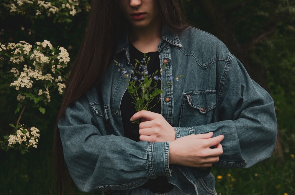 woman in blue denim jacket standing near green plants during daytime