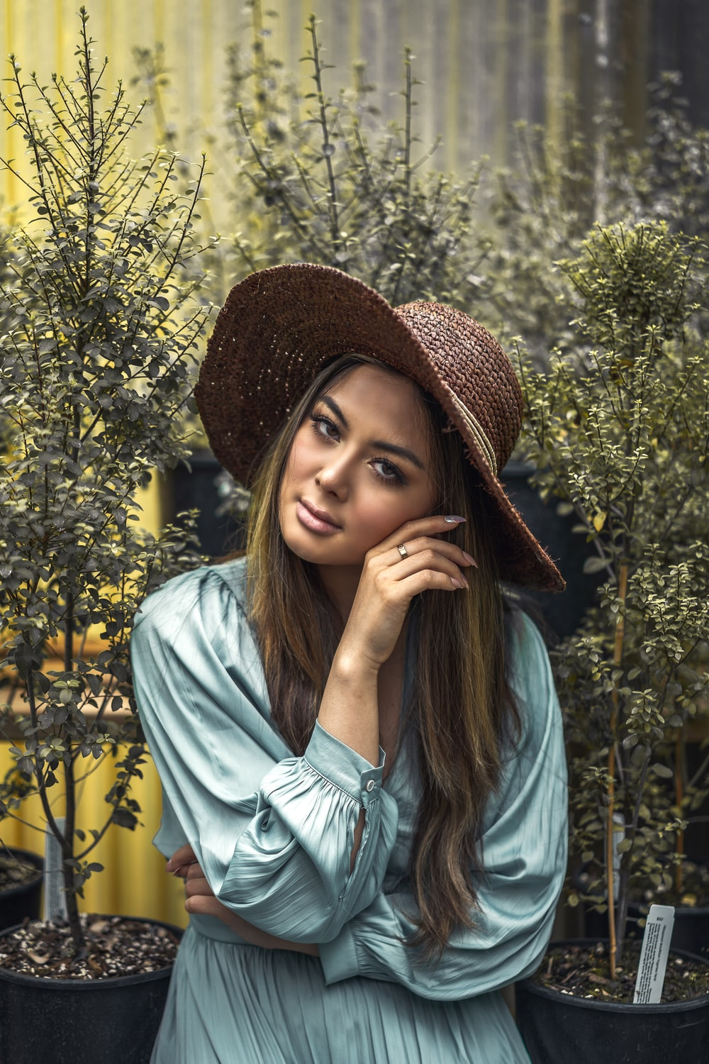 woman in blue dress shirt and brown hat standing near yellow flowers