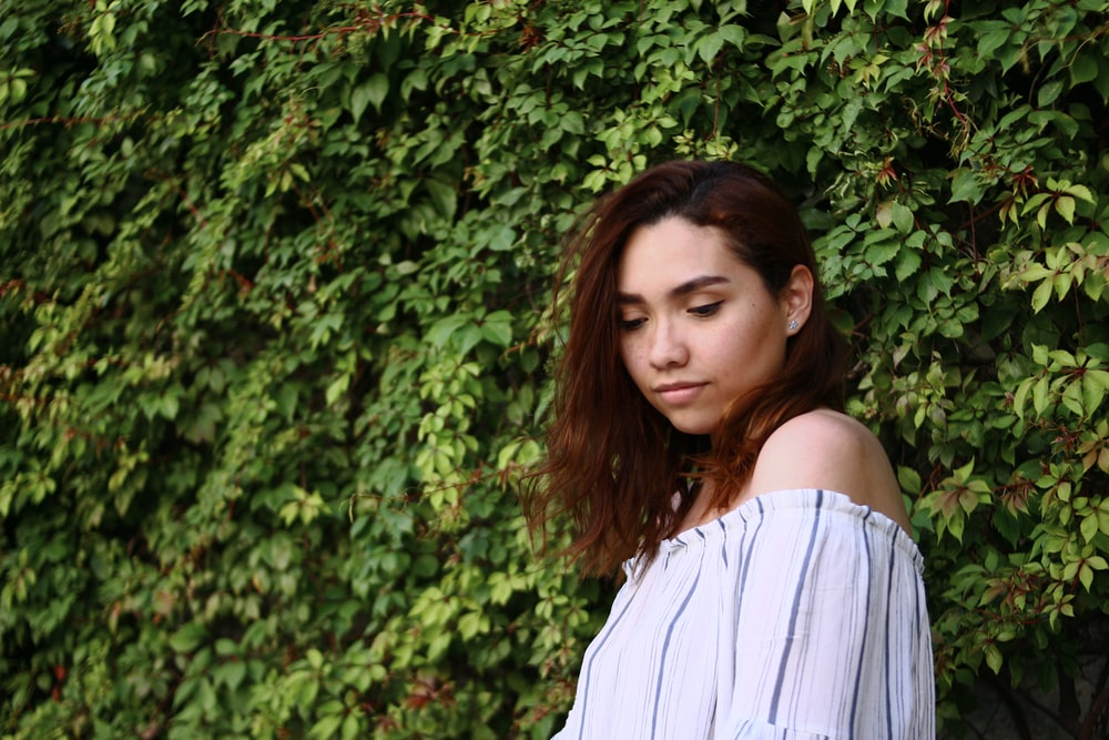 woman in white off shoulder shirt standing near green plant