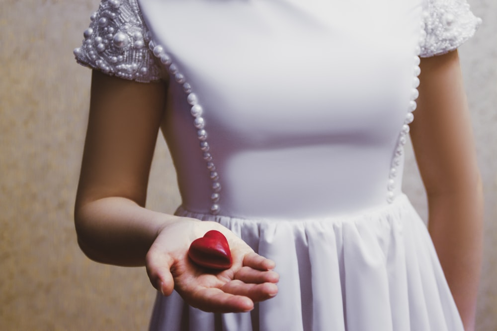 woman in white sleeveless dress holding red round fruit