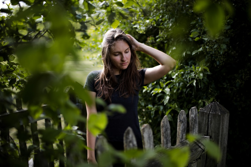 woman in black tank top standing beside wooden fence during daytime