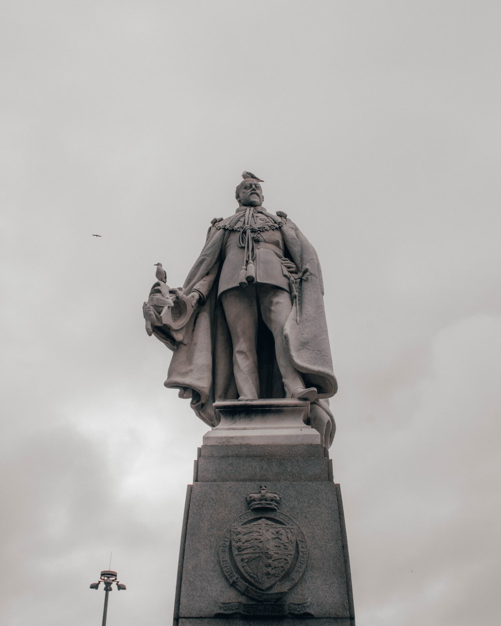 man in coat statue under white sky during daytime