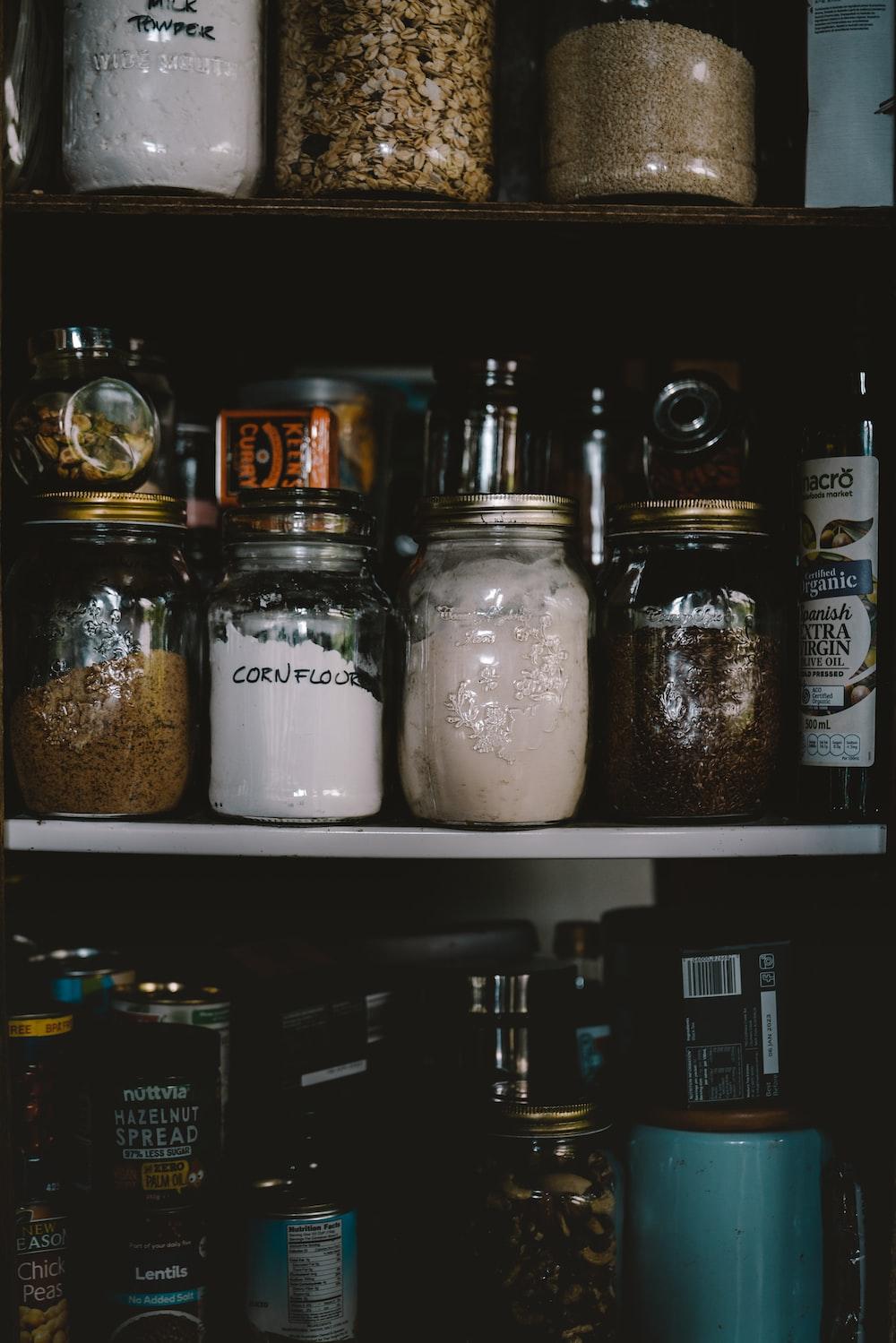 two clear glass jars on white shelf