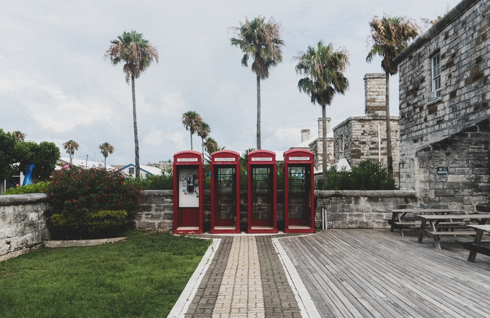 red telephone booth on green grass field near brown concrete building during daytime