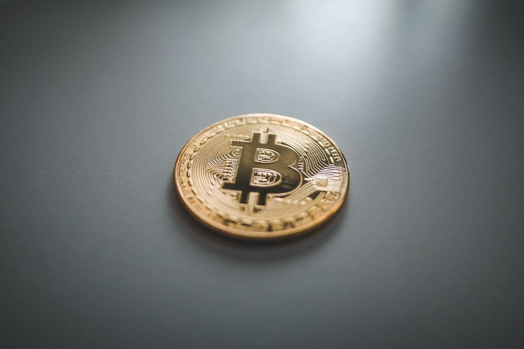 Physical Bitcoin (BTC) coin on white surface.