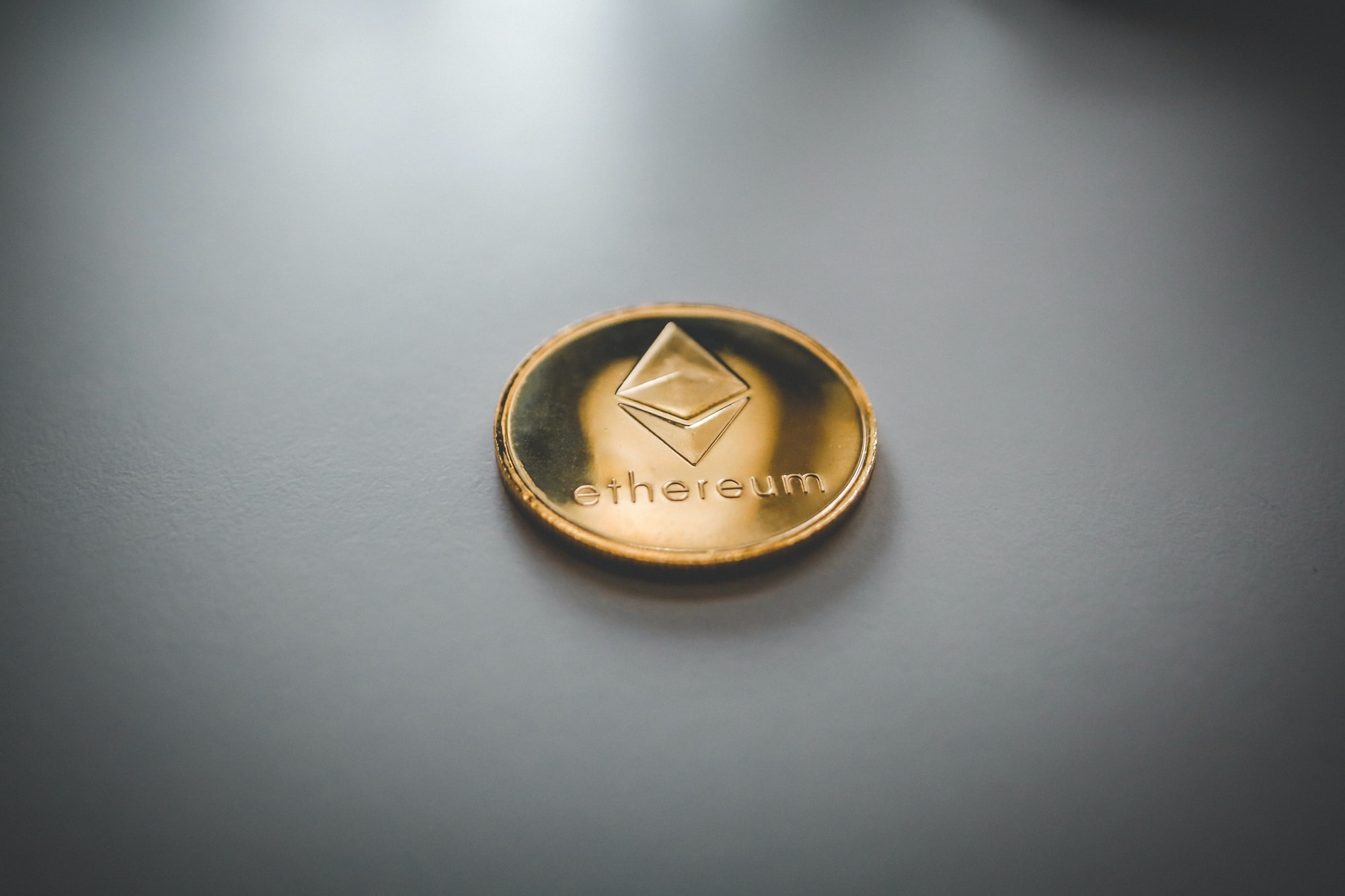Physical Ethereum (ETH) coin on white surface.