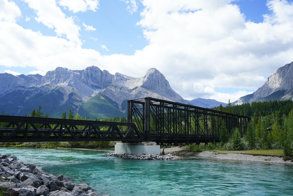 black wooden bridge over river near mountain range