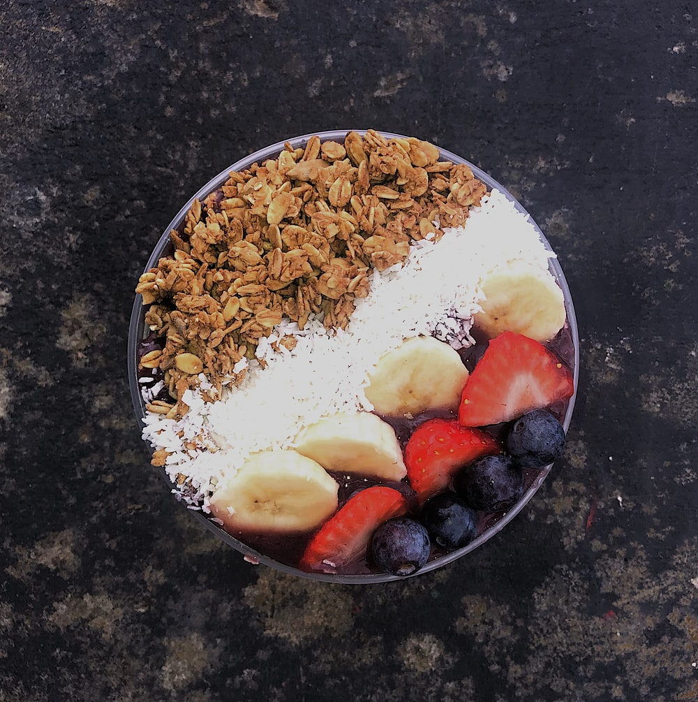 white rice with sliced strawberries and brown nuts on white ceramic plate