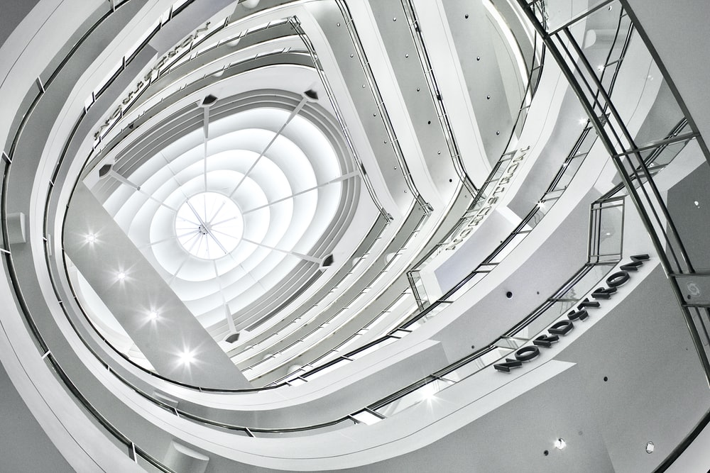 white spiral staircase in grayscale photography