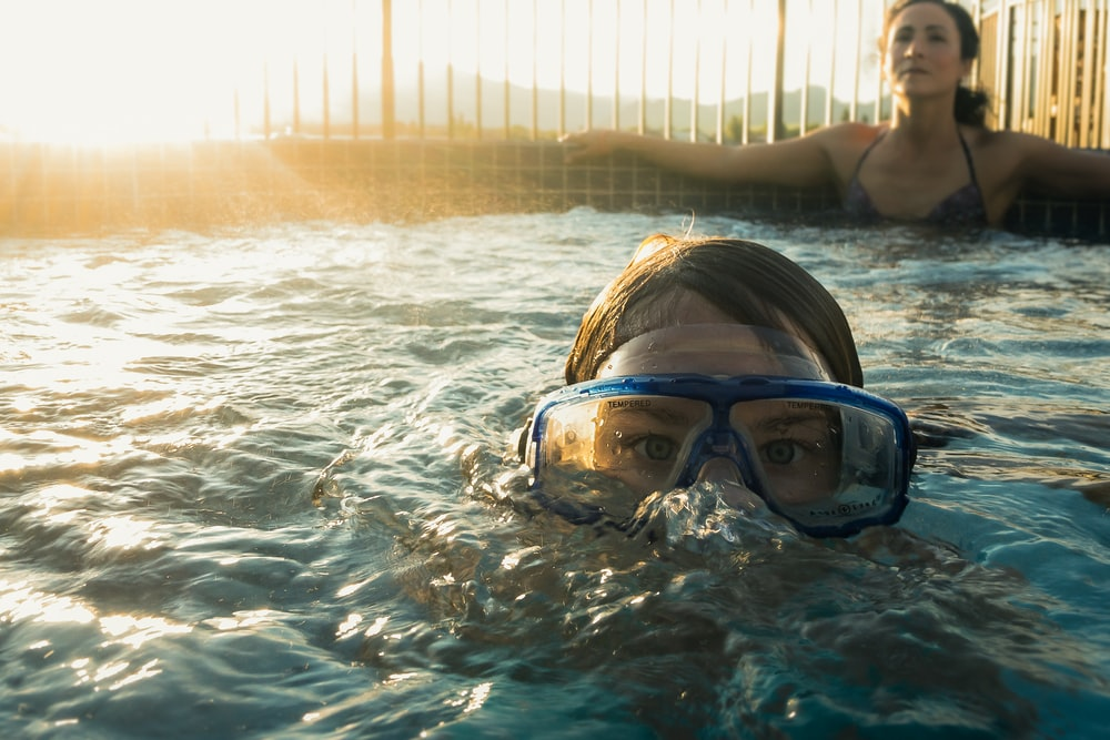 woman in blue swimming goggles in water during daytime