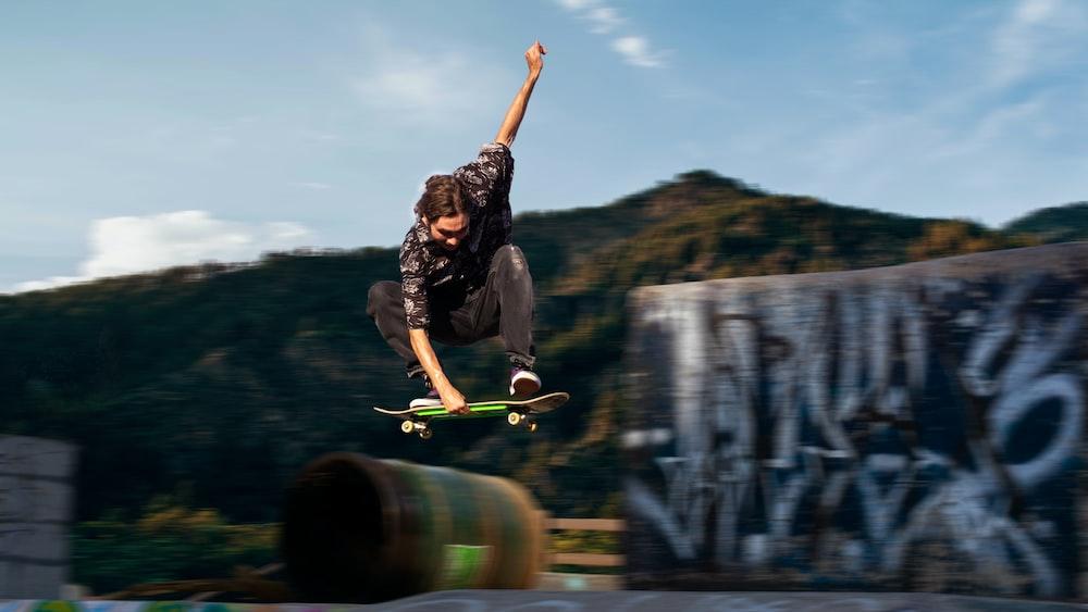 man in black t-shirt and black pants holding skateboard