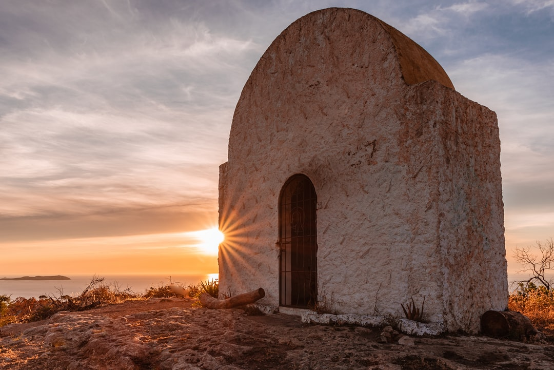 Sunset in front of an old Spanish chapel on a hill overlooking the sea.