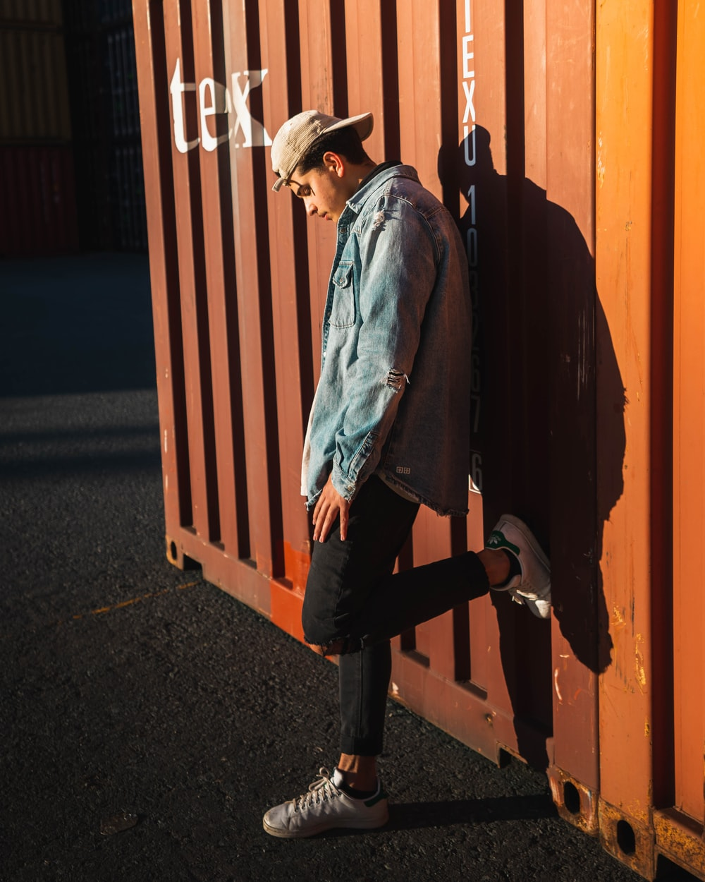 man in blue denim jacket and black pants standing beside brown wooden fence during daytime