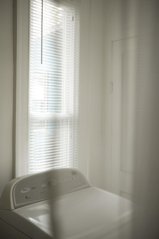 white window blinds near white bed