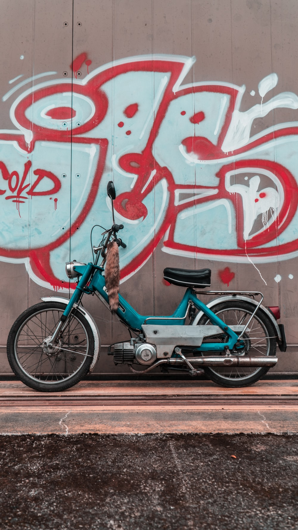 blue and black bicycle beside red wall