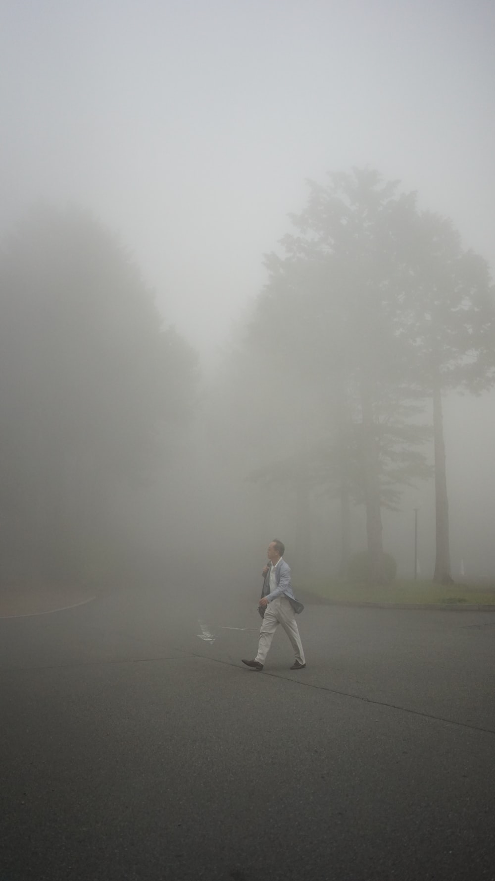woman in white jacket and gray pants standing on gray asphalt road during foggy weather