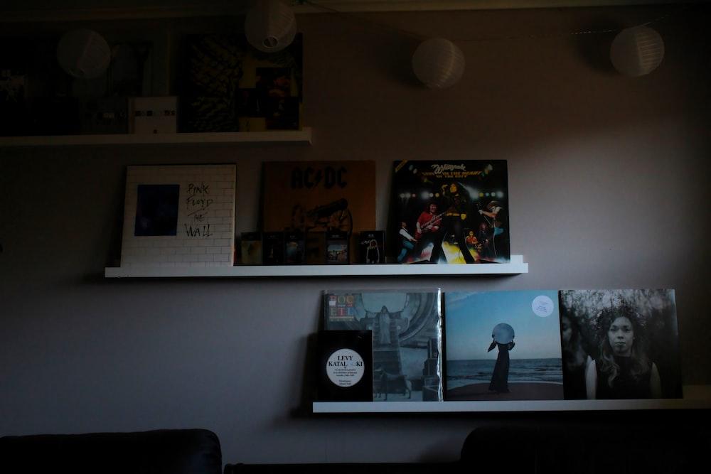 photos on white wall near black sofa