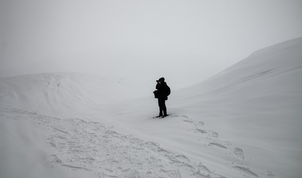 person in black jacket and pants walking on snow covered ground during daytime
