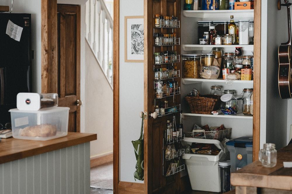 white plastic trash bin beside brown wooden shelf