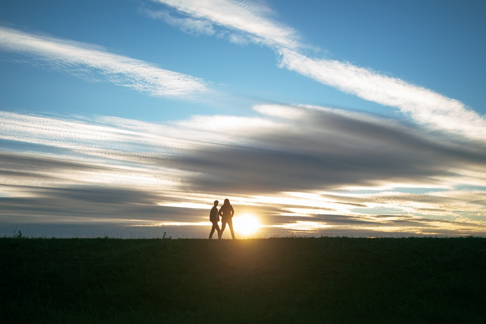 silhouette of 2 people walking on green grass field during sunset