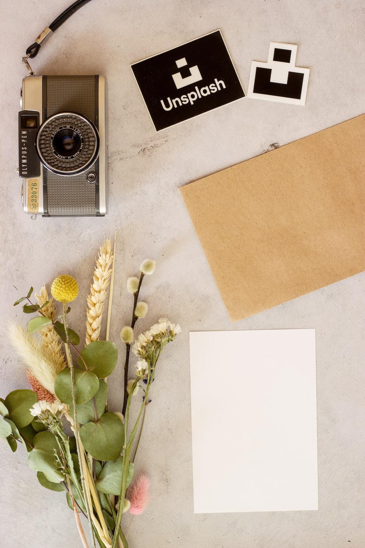 brown and black camera beside brown envelope