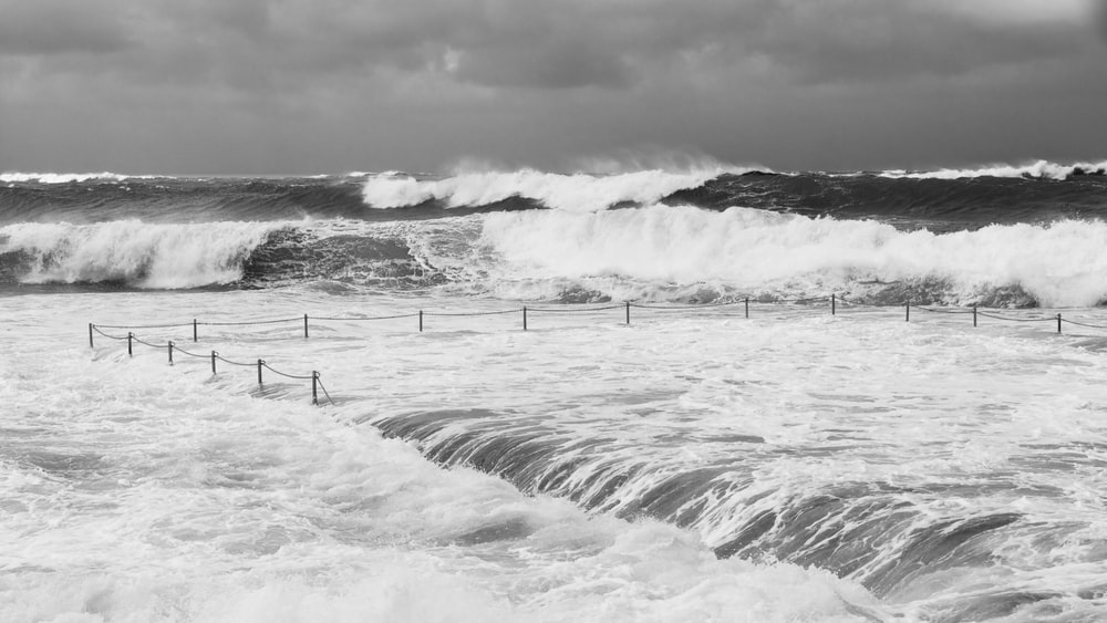 grayscale photo of sea waves crashing on shore