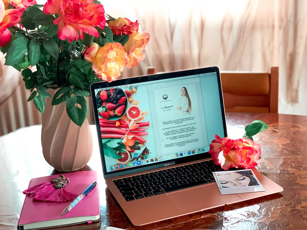 macbook pro beside red and yellow flowers