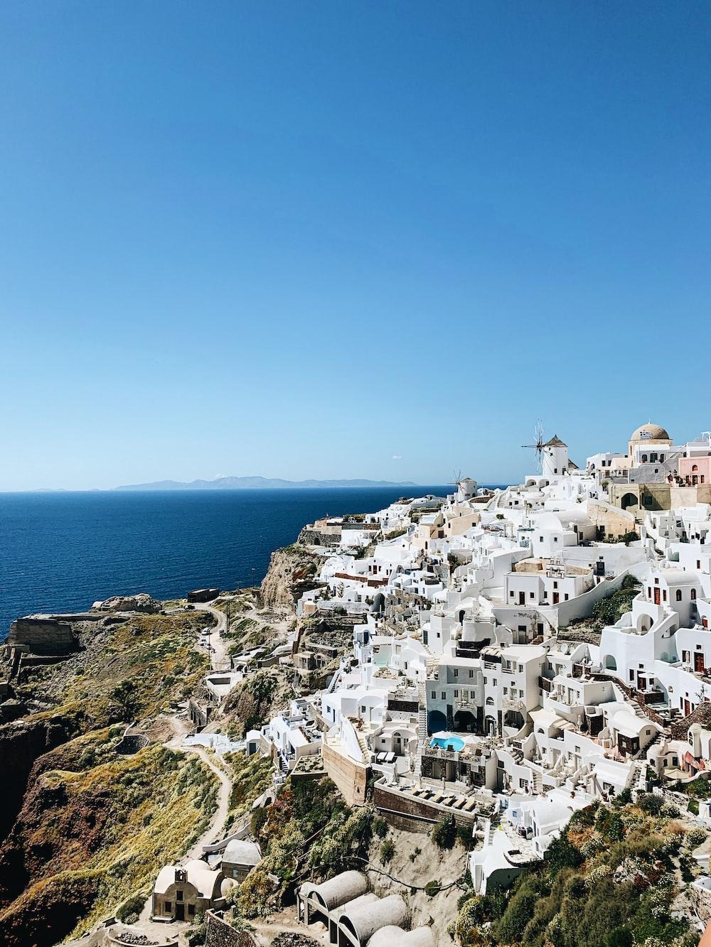 white concrete houses on mountain near sea during daytime