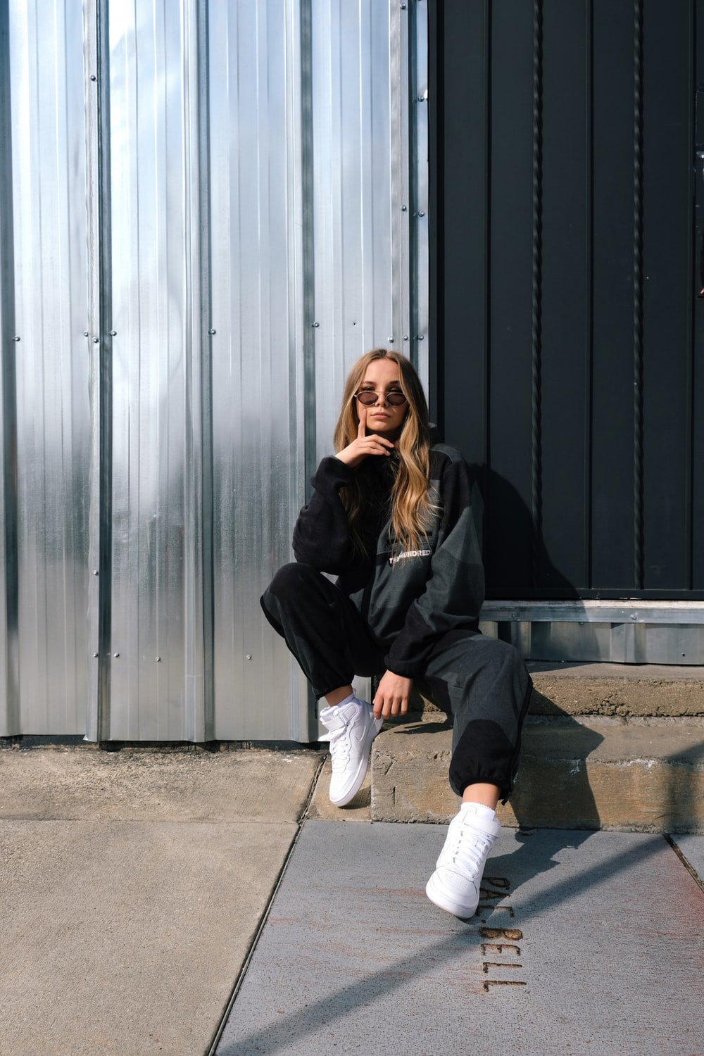 woman in black jacket and white pants sitting on gray concrete floor