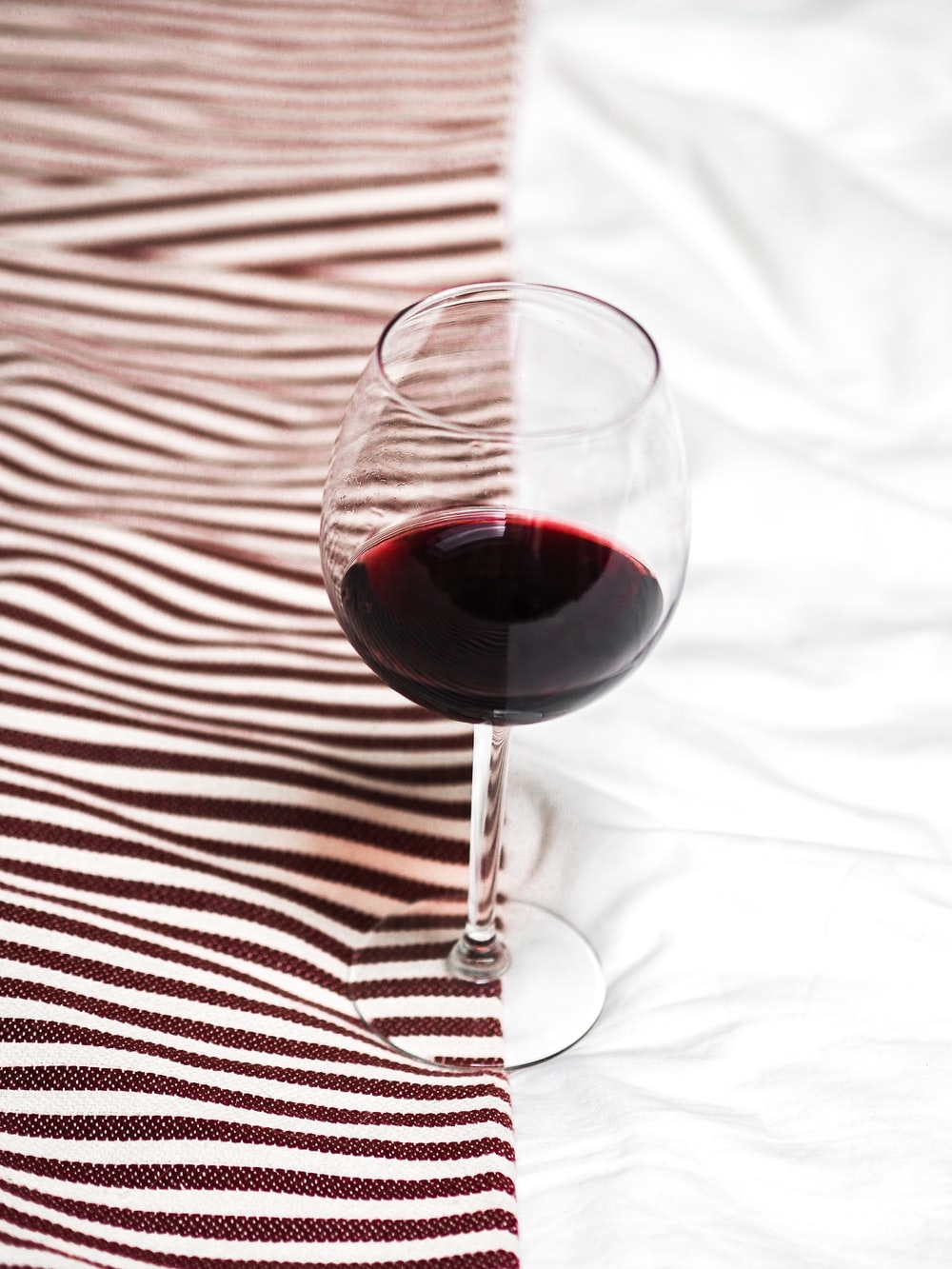 clear wine glass with red wine on white and black stripe textile