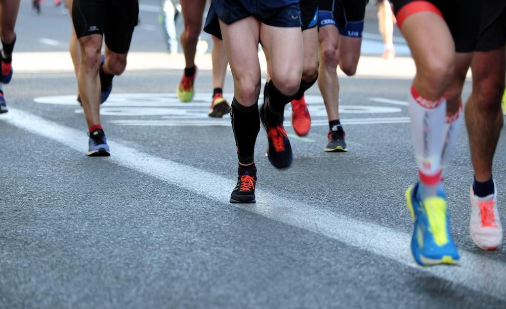 people running on gray asphalt road during daytime