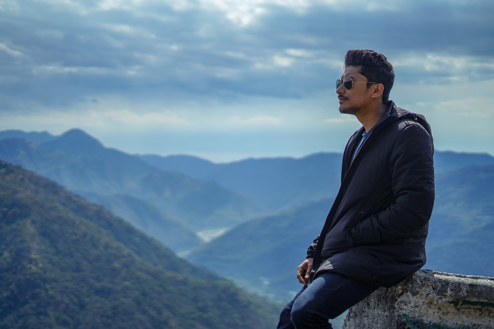 man in black jacket sitting on rock looking at the mountains during daytime