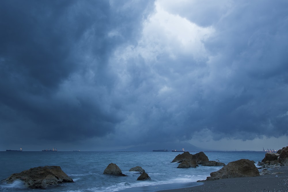 brown rock formation on sea under white clouds and blue sky during daytime