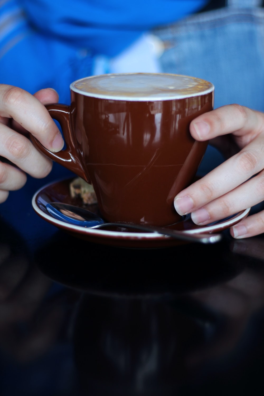 person holding brown ceramic mug