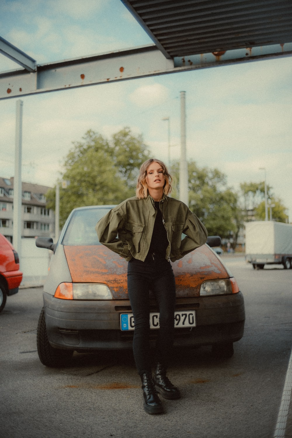 woman in brown jacket standing beside blue car during daytime