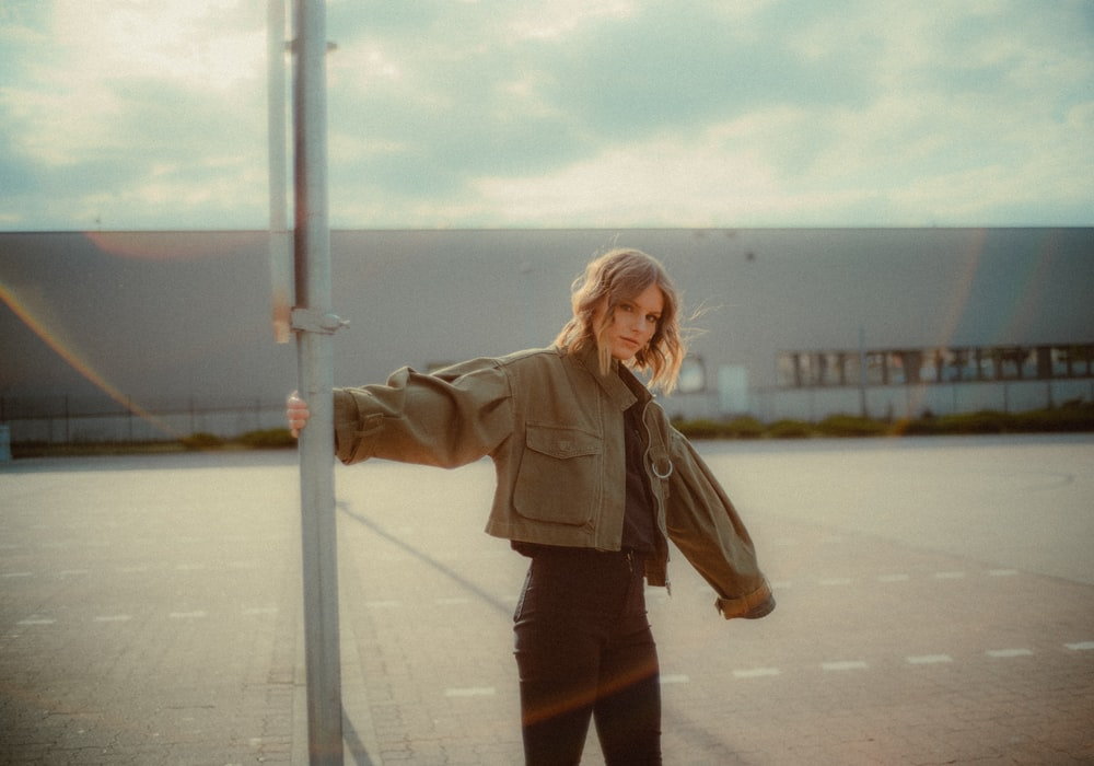 woman in brown jacket standing on gray concrete road during daytime