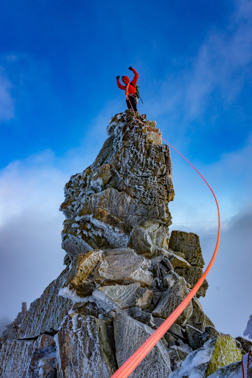 person in red jacket and black pants jumping on rocky mountain under blue sky during daytime