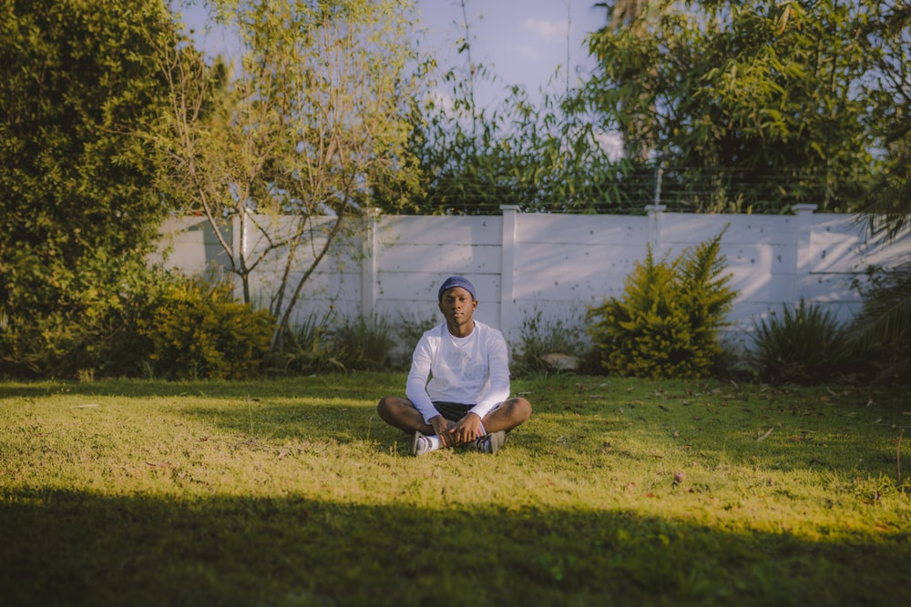 man in white crew neck t-shirt sitting on green grass field during daytime