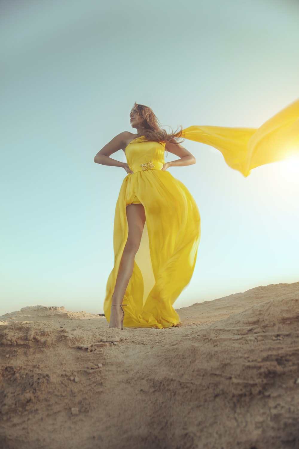 woman in yellow dress standing on brown sand during daytime