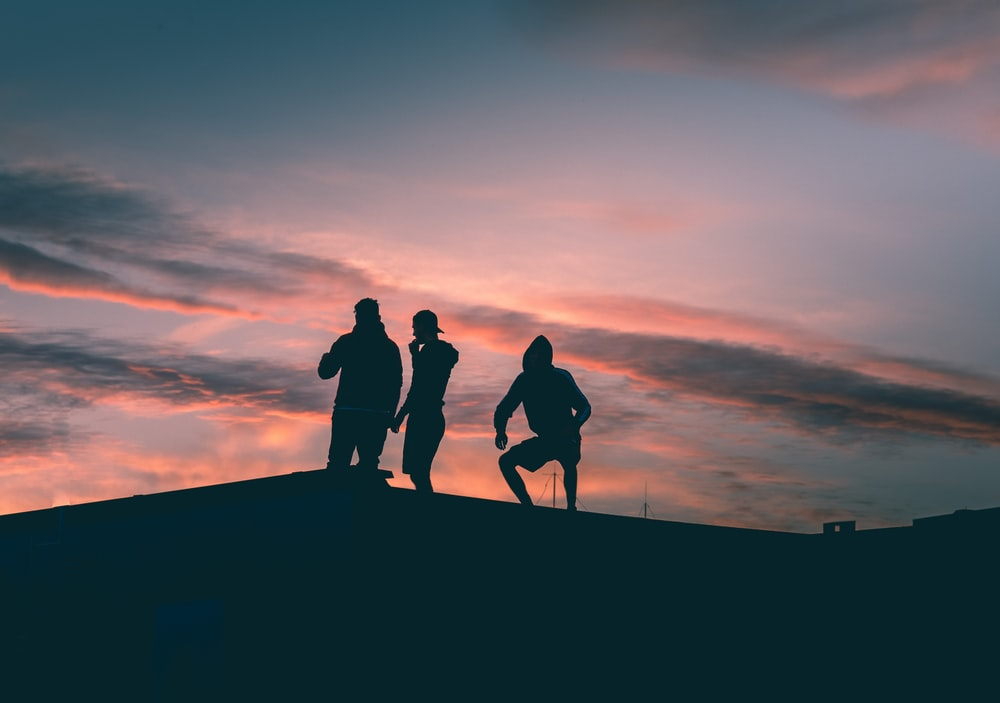 silhouette of 3 men standing on the edge of a hill during sunset