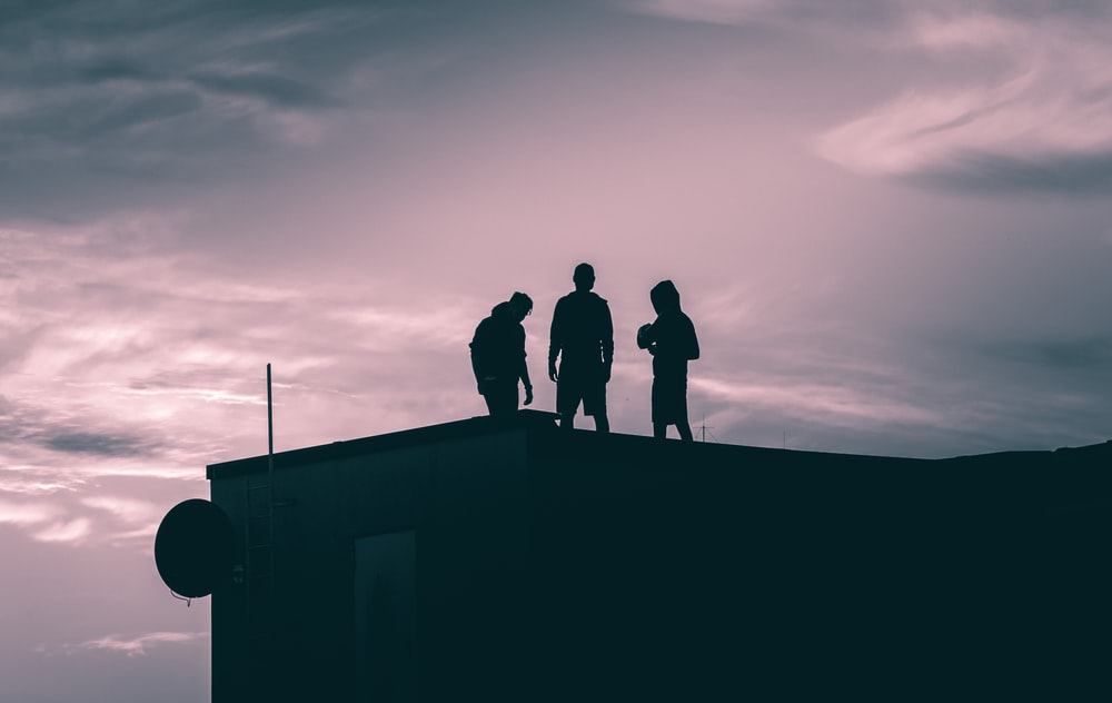 silhouette of 3 men standing on top of building during sunset